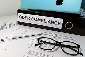 glasses and a pen on top of a piece of paper that has a GDPR compliance checklist for small businesses