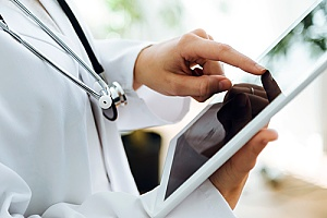 a doctor using an iPad to overcome common IT challenges