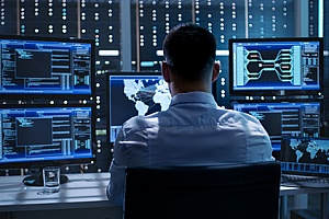 a cyber security official working on several monitors