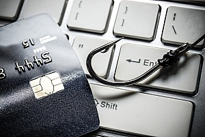 a fish hook and credit card on a keyboard representing a phishing attack