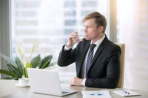 Employee drinking water in suit in home office
