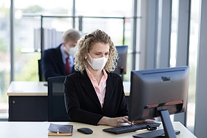 employee wearing a mask in the office during COVID-19
