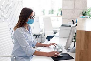 Masked employee sitting at desk