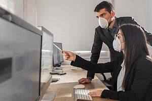 Masked employees looking at computer