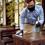 Small business owner cleaning tables