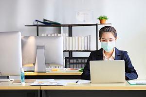 Woman in mask alone in office