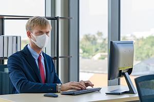 IT support worker in mask at desk