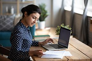 Woman at table remotely working