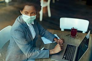 Employee in mask on laptop