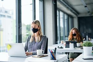 IT consultants at desks with masks