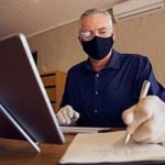 Small business owner in mask on computer