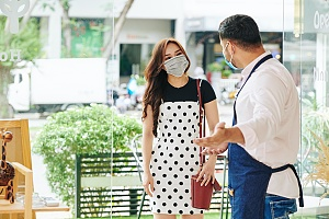 small business owner keeping up communication with his customers while wearing a mask